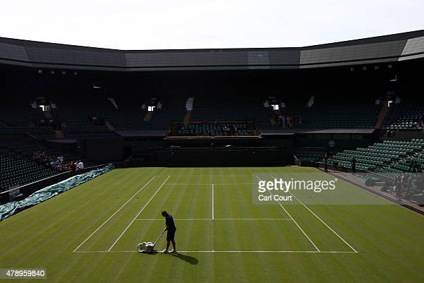 A groundsman paints a line on Centre Court on day 1 of the Wimbledon tennis tournament on June 29 2015 in London England The 129th tournament to be...