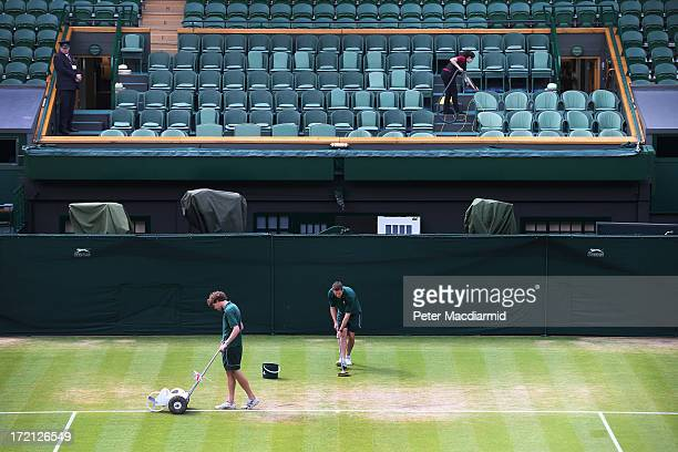 A groundsman paints the white lines and another uses a mop on the grass as a cleaner works in the royal box on Centre Court at the Wimbledon Lawn...