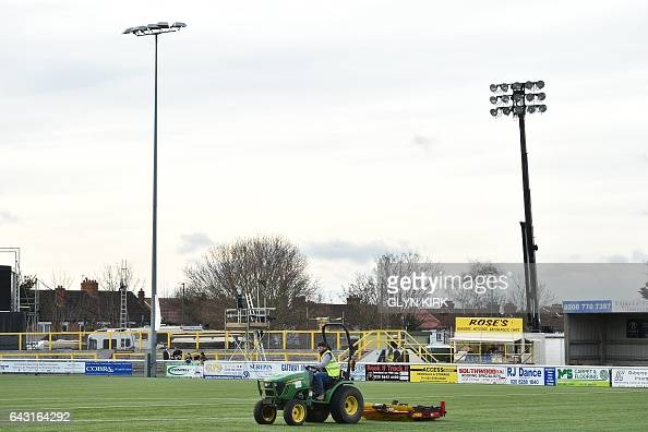 A groundsman prepares the artificial pitch ahead of the English FA Cup fifth round football match between Sutton United and Arsenal at the Borough...