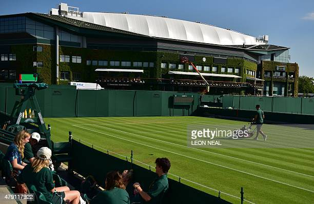 A groundsman prepares the grass on a tennis court ahead of play on day three of the 2015 Wimbledon Championships at The All England Tennis Club in...