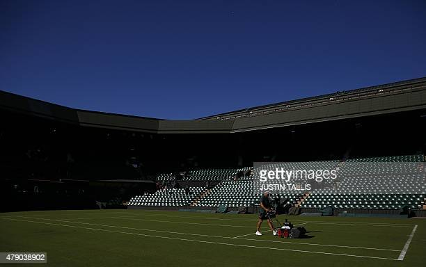 A groundsman prepares the grass on Centre Court ahead of play on day two of the 2015 Wimbledon Championships at The All England Tennis Club in...