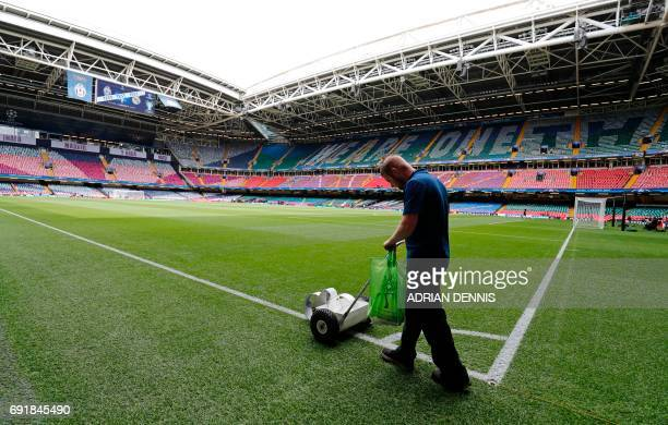 A groundsman puts the finishing touches to the pitch ahead of the UEFA Champions League final football match between Juventus and Real Madrid at The...