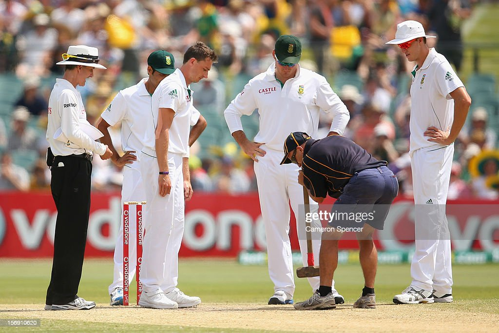A groundsman repairs the pitch for Dale Steyn of South Africa during day four of the Second Test Match between Australia and South Africa at Adelaide Oval on November 25, 2012 in Adelaide, Australia.
