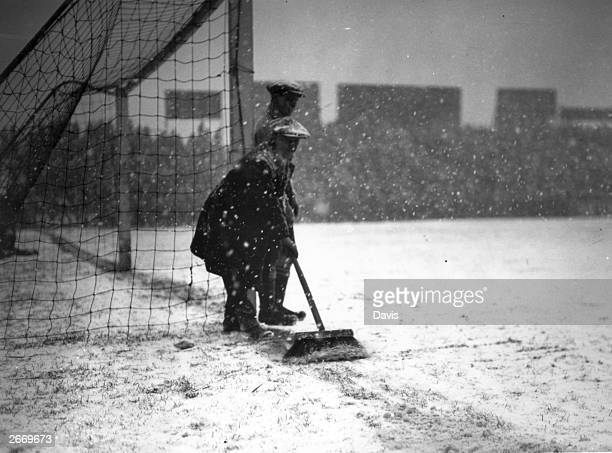A groundsman sweeps snow away from the goal line at Craven Cottage London before a FA Cup tie replay between Fulham and Everton