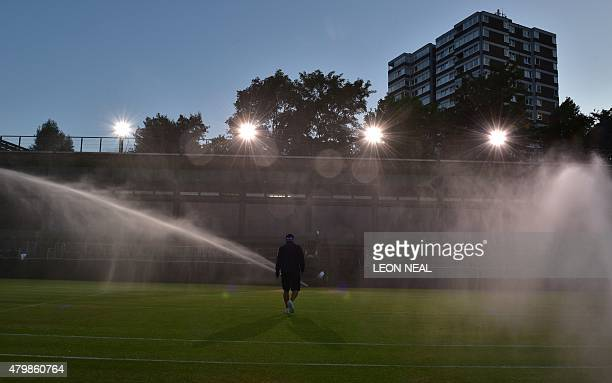 A groundsman walks on a court as the sprinklers water the grass at the end of day eight of the 2015 Wimbledon Championships at The All England Tennis...