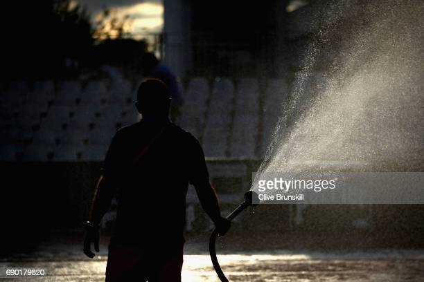 A groundsman waters the courts on day three of the 2017 French Open at Roland Garros on May 30 2017 in Paris France