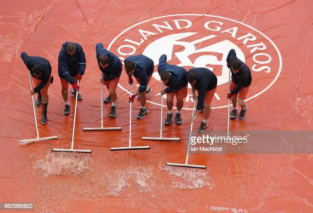 Groundsmen clear the court after rain stopped play at the Suzanne Lenglen Court during the match between Jelena Ostapenko of Latvia and Caroline...