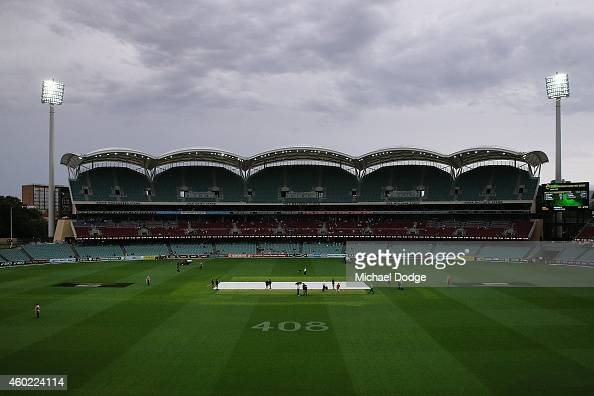 Groundsmen cover the pitch during a rain delay during day two of the First Test match between Australia and India at Adelaide Oval on December 10...