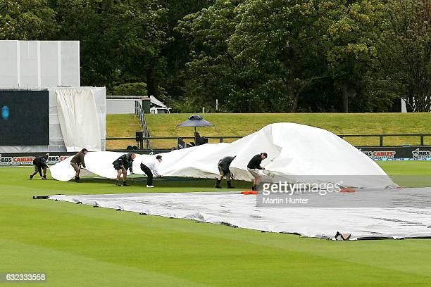 Groundsmen pull the covers over the wicket as rain delays play during day three of the Second Test match between New Zealand and Bangladesh at Hagley...