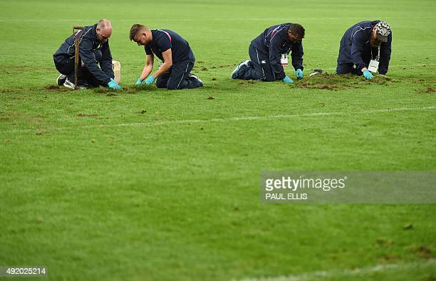 Groundsmen repair the pitch at half time during a Pool C match of the 2015 Rugby World Cup between New Zealand and Tonga at St James' Park in...