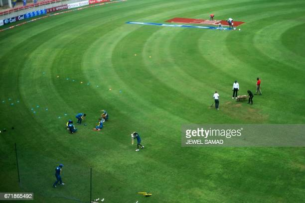 Groundsmen spread sand over part of the wet outfield as Pakistan's cricketers warm up before the start of day three of the first Test match between...
