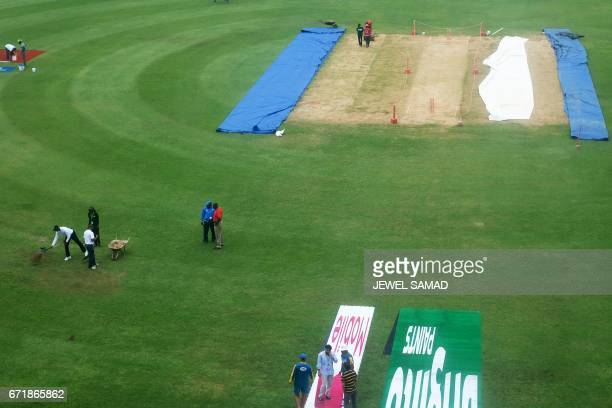 Groundsmen spread sand over part of the wet outfield before the start of day three of the first Test match between West Indies and Pakistan at the...
