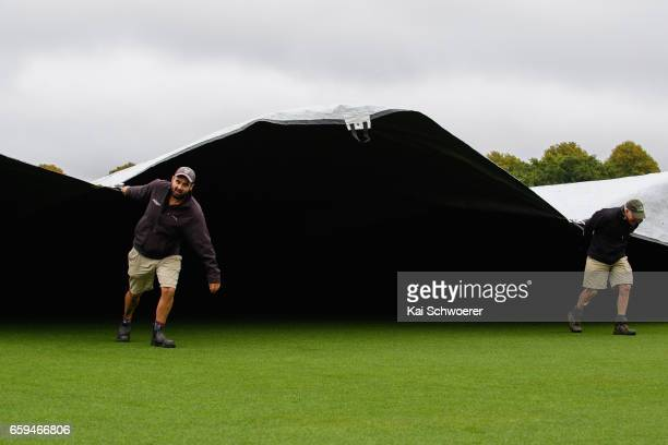 Groundsmen struggle to control the rain covers as rain delays play during the Plunket Shield match between Canterbury and Wellington on March 29 2017...