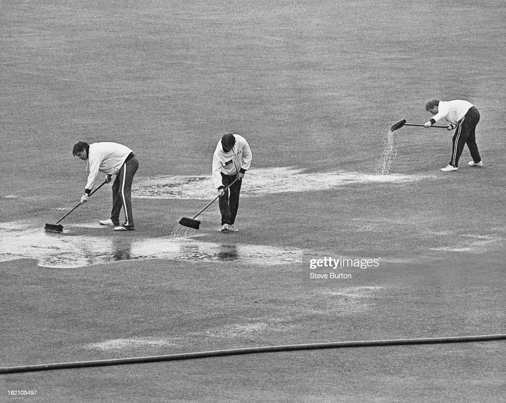 Groundsmen sweep the water off the pitch at Lord's Cricket Ground in northwest London after a period of heavy rainfall 3rd August 1979