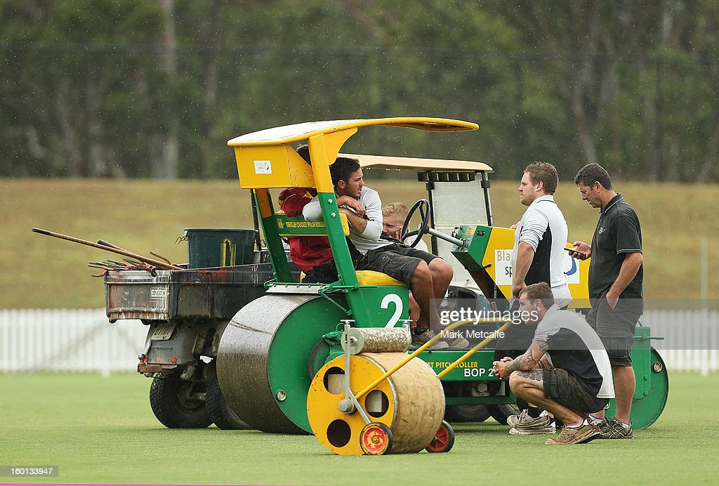 Groundsmen wait in the outfield as rain delays the start of day four of the Sheffield Shield match between the New South Wales Blues and the Western Australia Warriors at Bankstown Oval on January 27, 2013 in Sydney, Australia.