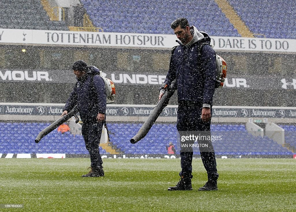"""Groundstaff attempt to clear the pitch of snow for kick off during an English Premier League football match between Tottenham Hotspur and Manchester United at White Hart Lane in London, England, on January 20, 2013. AFP PHOTO/Ian KINGTON - RESTRICTED TO EDITORIAL USE. No use with unauthorized audio, video, data, fixture lists, club/league logos or """"live"""" services. Online in-match use limited to 45 images, no video emulation. No use in betting, games or single club/league/player publications."""