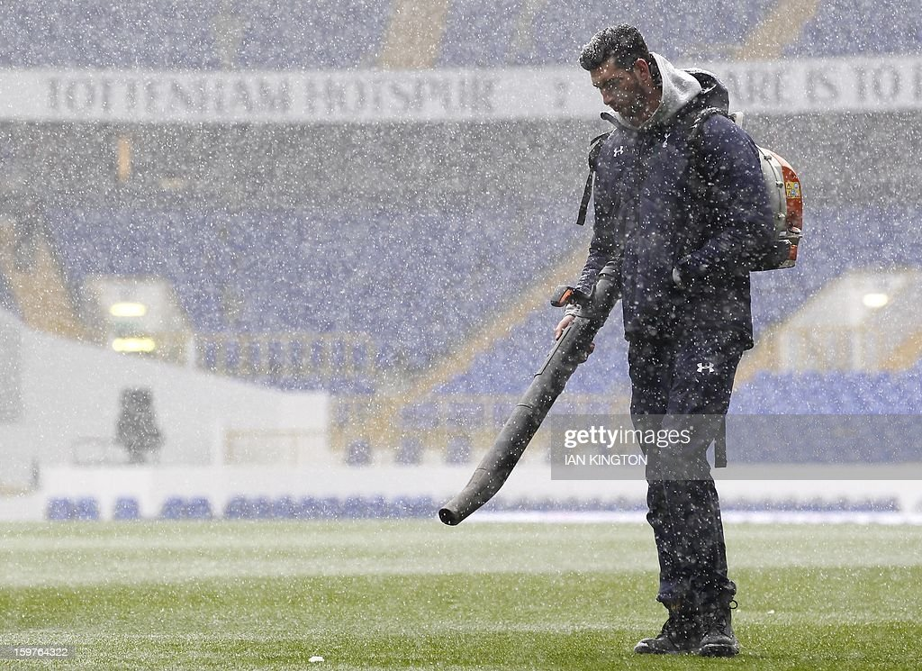 "Groundstaff attempt to clear the pitch of snow for kick off during an English Premier League football match between Tottenham Hotspur and Manchester United at White Hart Lane in London, England, on January 20, 2013. AFP PHOTO/Ian KINGTON - RESTRICTED TO EDITORIAL USE. No use with unauthorized audio, video, data, fixture lists, club/league logos or ""live"" services. Online in-match use limited to 45 images, no video emulation. No use in betting, games or single club/league/player publications."