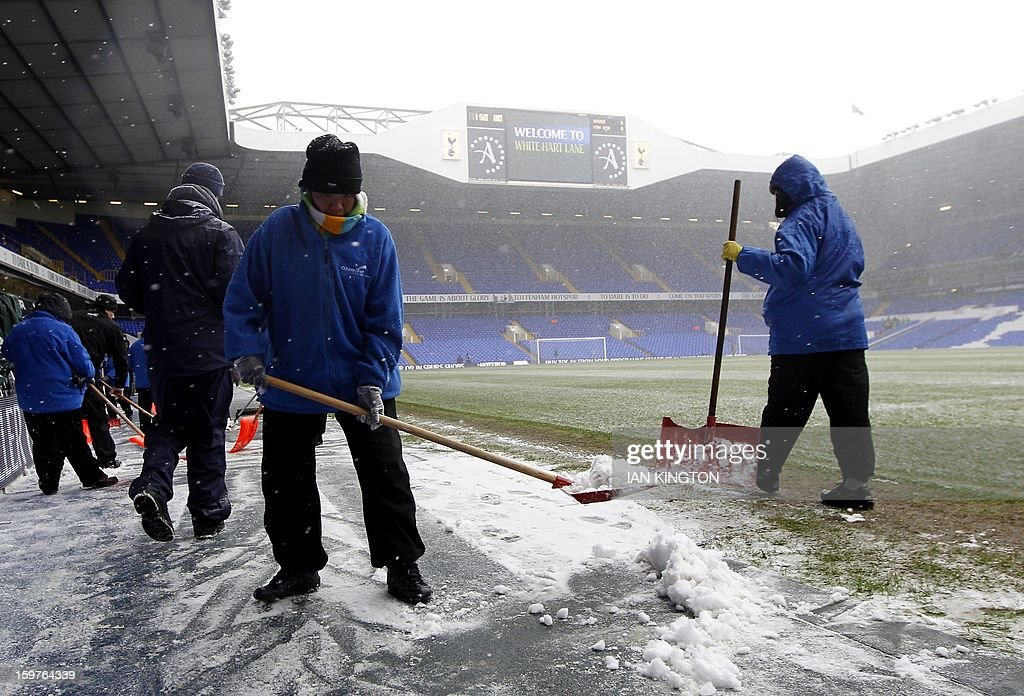 Groundstaff attempt to clear the pitch of snow for kick off for an English Premier League football match between Tottenham Hotspur and Manchester United at White Hart Lane in London, England, on January 20, 2013. AFP PHOTO/Ian KINGTON - RESTRICTED TO EDITORIAL USE. No use with unauthorized audio, video, data, fixture lists, club/league logos or live services. Online in-match use limited to 45 images, no video emulation. No use in betting, games or single club/league/player publications.