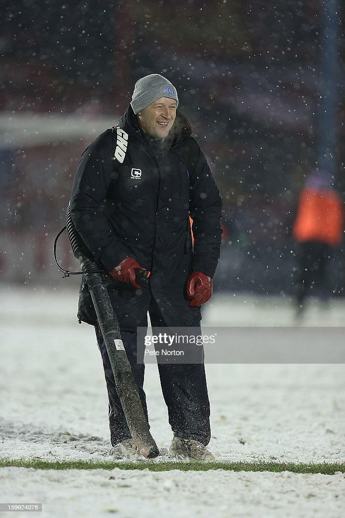 Groundstaff clear snow from the touchline during half time of the npower League Two match between Aldershot Town and Northampton Town at the EBB Stadium on January 22, 2013 in Aldershot, England.