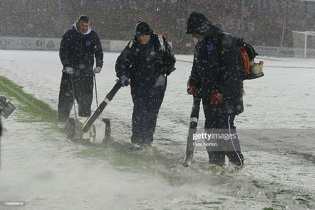 Groundstaff clear the touchline from snow covered pitch the EBB Stadium prior to the npower League Two match between Aldershot Town and Northampton Town at the EEB Stadium on January 22, 2013 in Aldershot, England.
