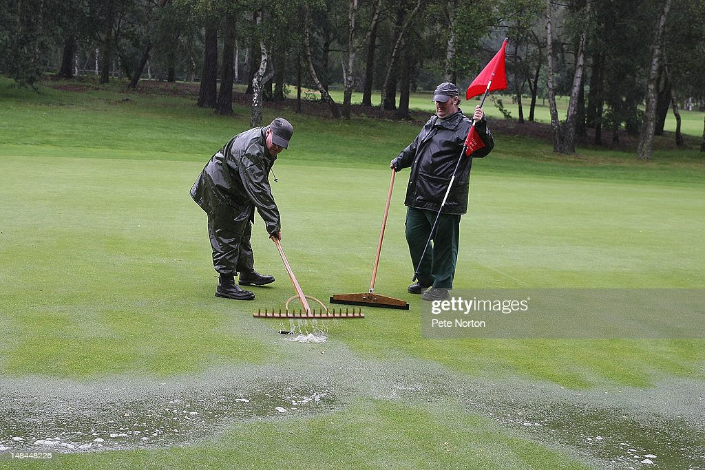 Groundstaff clear water from the 18th green after persistant rain during the Virgin Atlantic PGA National Pro-Am Championship - Regional Final at Kings Lynn Golf Club on July 16, 2012 in King's Lynn, England.