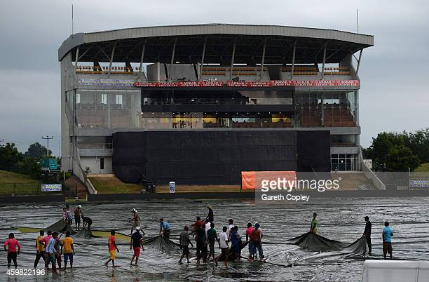 Groundstaff cover the field during a thunderstorm which caused England's nets session to be cancelled at Mahinda Rajapaksa International Stadium on...