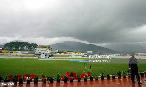 A groundstaff member walks along the boundary as clouds gather over the pitch on the final day of a three day match between Pakistan and an Indian...