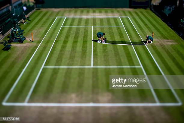 Groundstaff prepare the courts ahead of the start of play on day seven of Wimbledon Lawn Tennis Championships at the All England Lawn Tennis and...