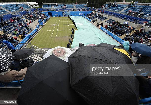 Groundstaff pull on the covers on The Ann Jones Centre Court as the rain comes down during the match between Sorana Cirstea of Romania and Donna...