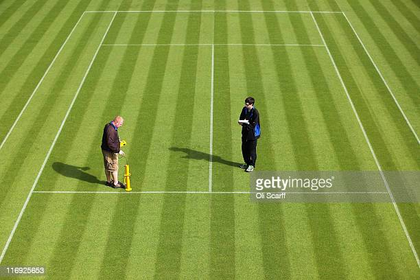 Groundstaff use an instrument to check the bounciness of the grass courts at the All England Lawn Tennis and Croquet Club ahead of the Wimbledon Lawn...