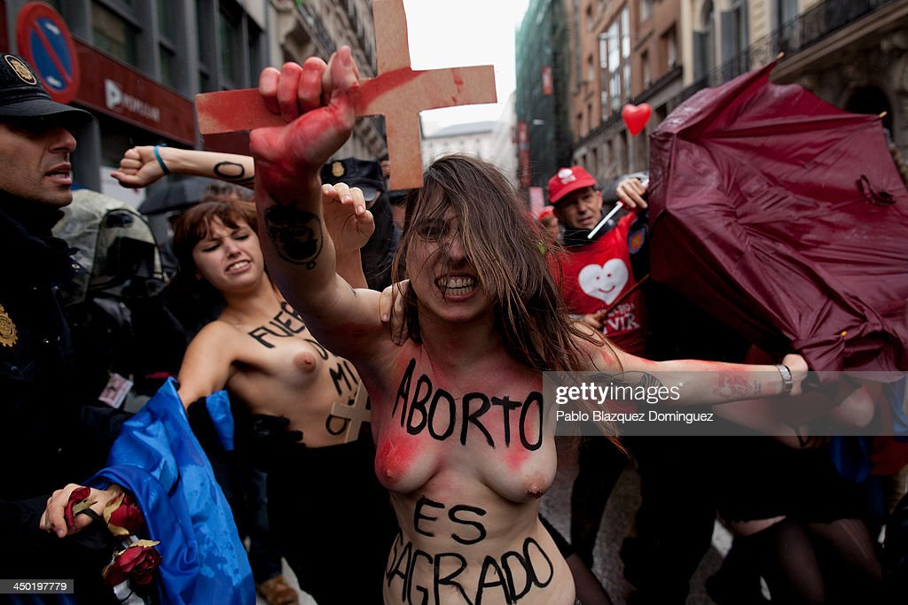 FEMEN group activists shout slogans topless as a Pro-Life demonstration takes place on Alcala Street on November 17, 2013 in Madrid, Spain. Body painting reads 'Abortion is sacred'. The Pro-Life rally was demonstrating against women's right to abort.