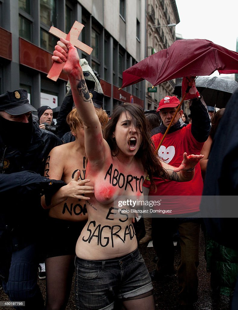 FEMEN group activists with body painting reading 'abortion is sacred' shout slogans and holds a cross as a Pro-Life demonstration takes place on Alcala Street on November 17, 2013 in Madrid, Spain. The Pro-Life rally was demonstrating against women's right to abort.