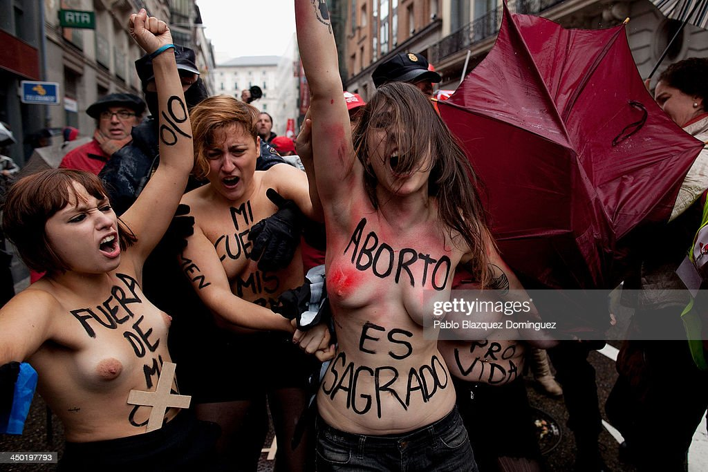 FEMEN group activists with body paintings (2R) reading 'abortion is sacred' or (L) 'get out of my body' shout slogans as a Pro-Life demonstration takes place on Alcala Street on November 17, 2013 in Madrid, Spain. The Pro-Life rally was demonstrating against women's right to abort.