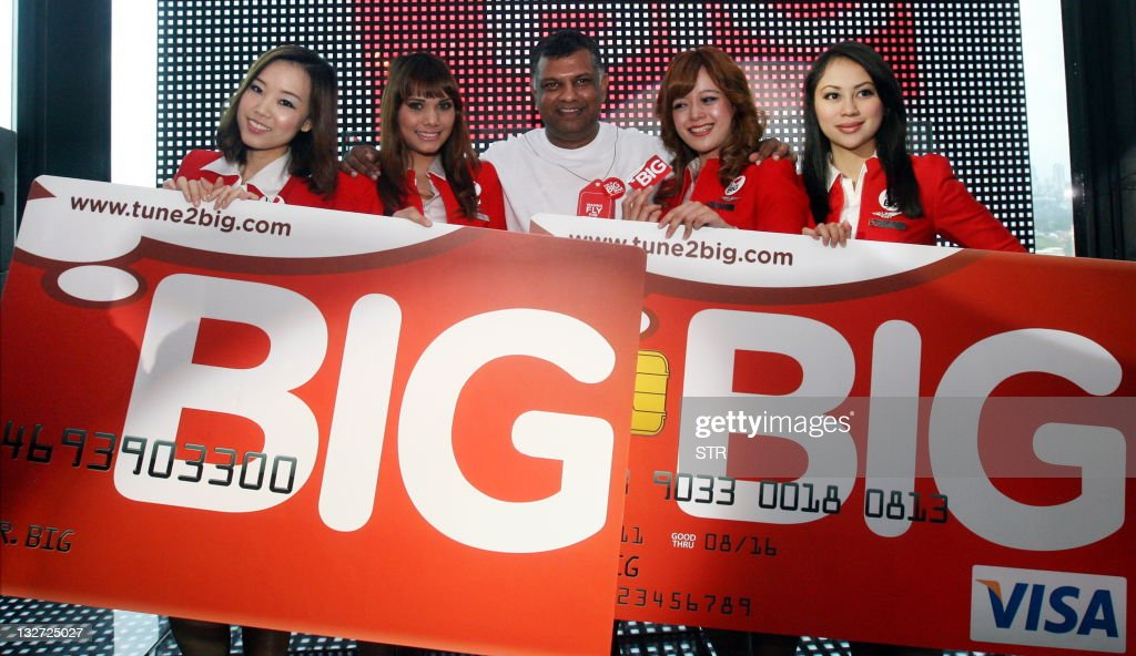 Group CEO of AirAsia Tony Fernandes and stewardess pose with a BIG Visa prepaid card during its launch in Kuala Lumpur on November 14, 2011. Fernandes said the BIG launch was a major breakthrough as the company seeks to reward itsr loyal guests and customers.