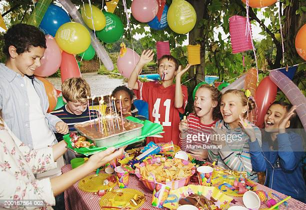 Group children (9-12) at birthday party outdoors
