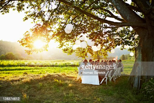 Group dining around table outside in field : Stock Photo
