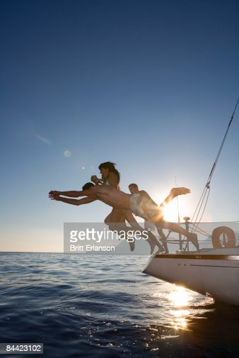 Group dive off back of sailboat : Stock Photo