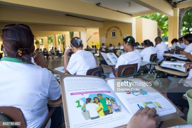 Santo Domingo Dominican Republic December 02 2012 A group educational lesson for volunteers reading a book about home visiting for a auxiliary...