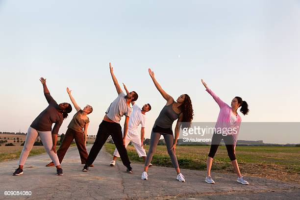 Group exercising Yoga outdoors at sunset