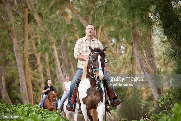 A group explores a trail on horseback