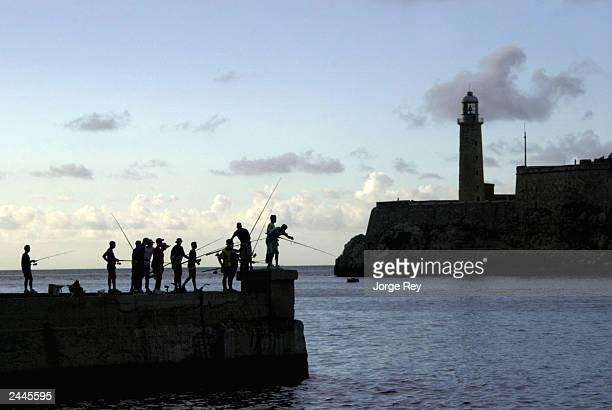 A group fishes on the Malecon waterfront August 29 2003 in Havana Cuba The island nation faces a deep economic crisis in a dispute with the European...
