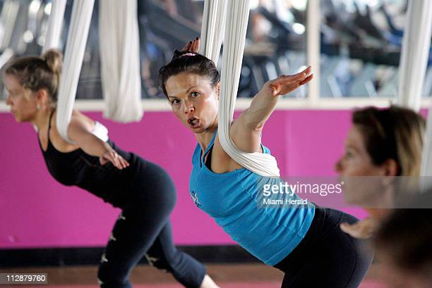 Group fitness coordinator Robin Retherford center and gives instructions during an Antigravity Yoga with Wings class at Crunch Fitness in Miami Beach...