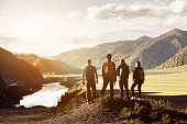 Group of four people stands on mountains and river backdrop. Travel expedition trekking concept with space for text
