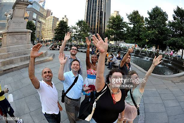 A group gathered at Columbus Circle 'wave at Saturn' on July 19 2013 while the NASA Cassini probe orbiting Saturn takes a photograph of the ringed...