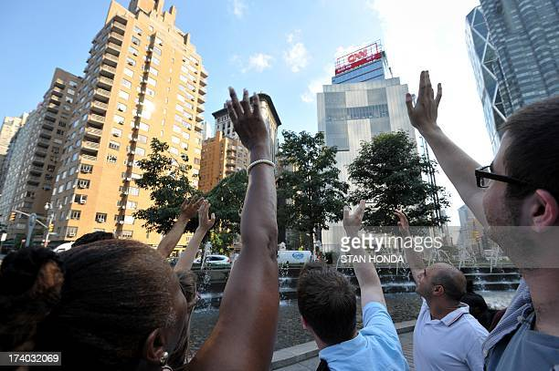 A group gathers at Columbus Circle in New York for a 'wave at Saturn' on July 19 2013 while the NASA Cassini probe orbiting Saturn takes a photograph...