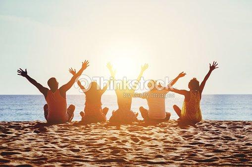 Group happy people beach sea sunset concept : Stock Photo