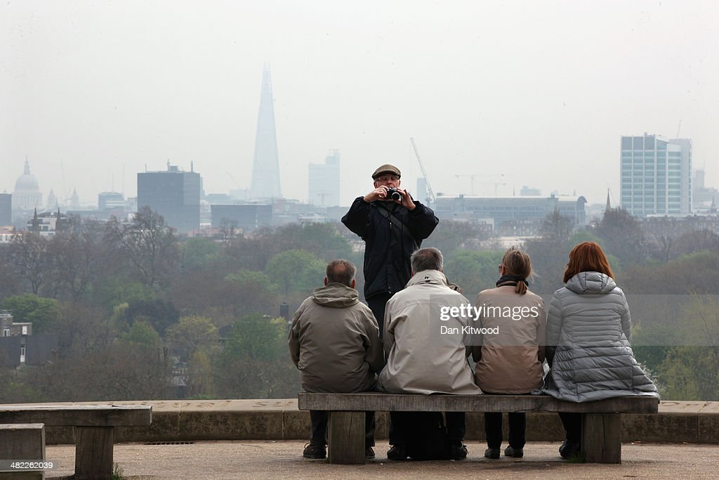 A group have their photograph taken at the top of Primrose Hill with the London skyline in the background on April 3 2014 in London England Dust from...