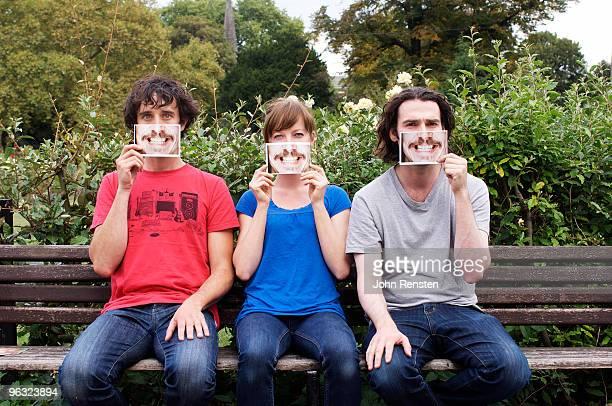 group hiding behind fake paper masks smiling