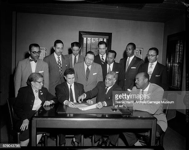 Group in Pittsburgh Courier newspaper office including Frank Lavelle Russell Washington Mal Goode Clyde Page and Hubert Smith standing in back row...