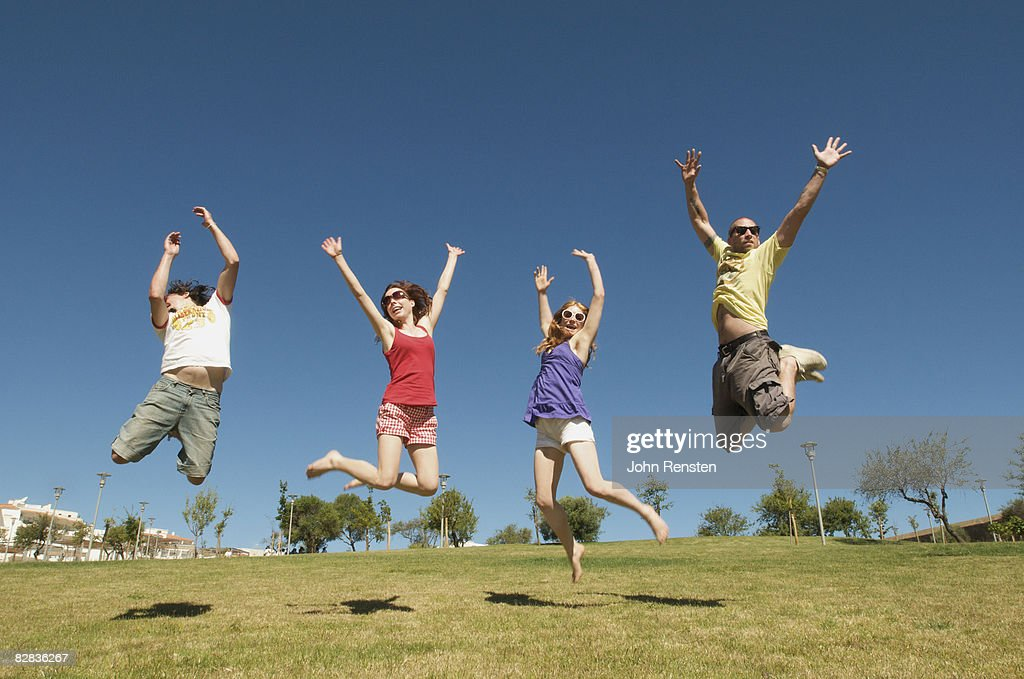 group jumping in the sunshine on a hill : Stock Photo